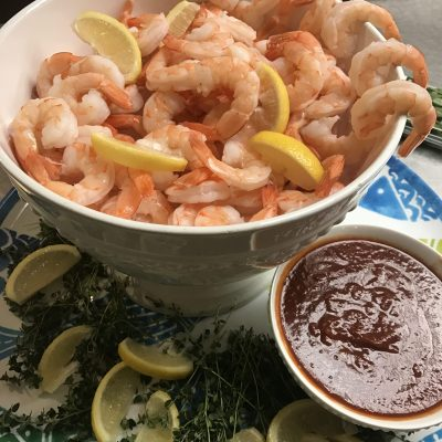 bowl of shrimp with lemon and cocktail sauce