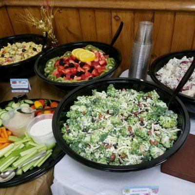 bowls of broccoli salad, fruit salad, tortellini, salad, and potato salad at a graduation party